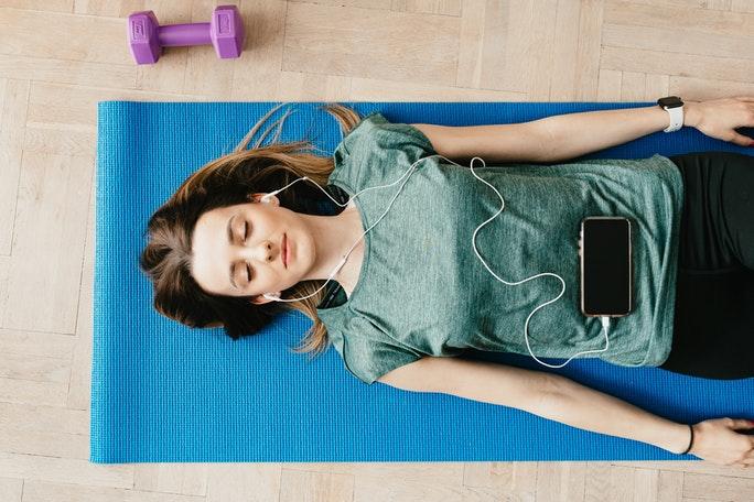 Frau liegt auf Yogamatte während Progressiver Muskelentspannung