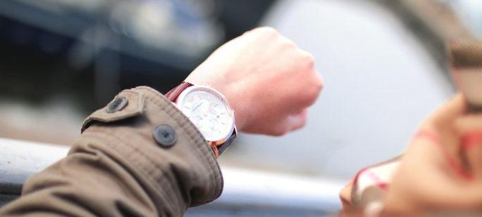 Frau die auf die Uhr schaut weil sie gestresst ist - keine Zeit für Entspannungsübungen