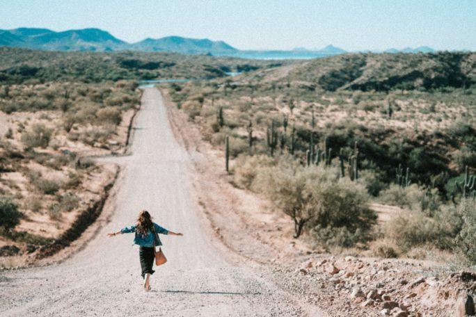 Frau in der Wüste geht auf einer Straße und macht Gehmeditation