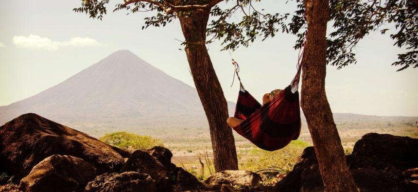 Progressive Muskelentspannung nach Jacobson: Frau liegt entspannt in der Hängematte