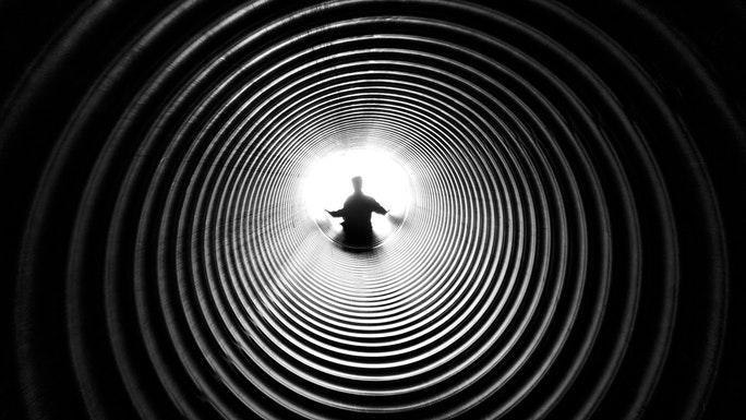 Dunkler Tunnel mit Mensch in Meditation und Licht am Ende