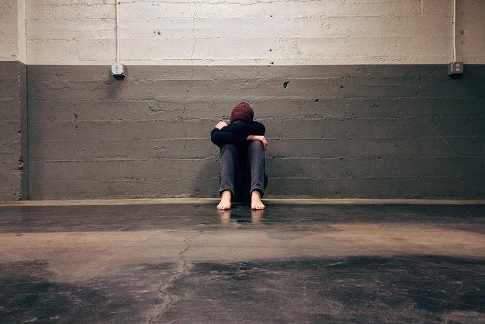 Junge unter Stress kauert sich vor einer Wand zusammen weil er kein Stressmanagement anwenden kann