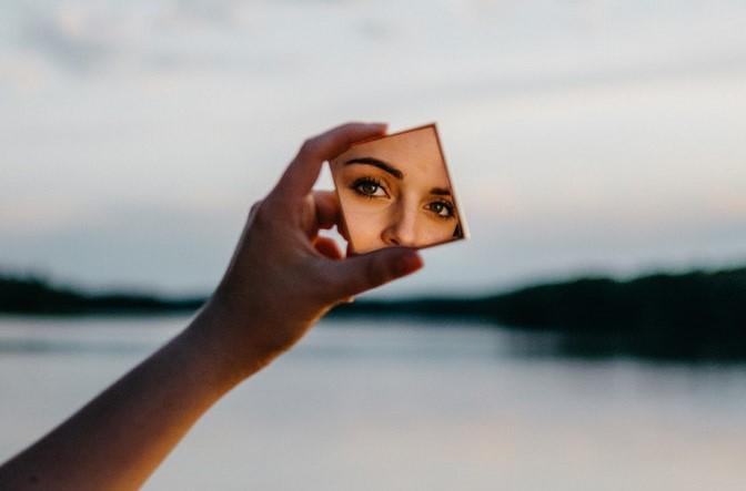 Selbstreflexion Frau im Spiegel mit Wasser im Hintergrund querformat